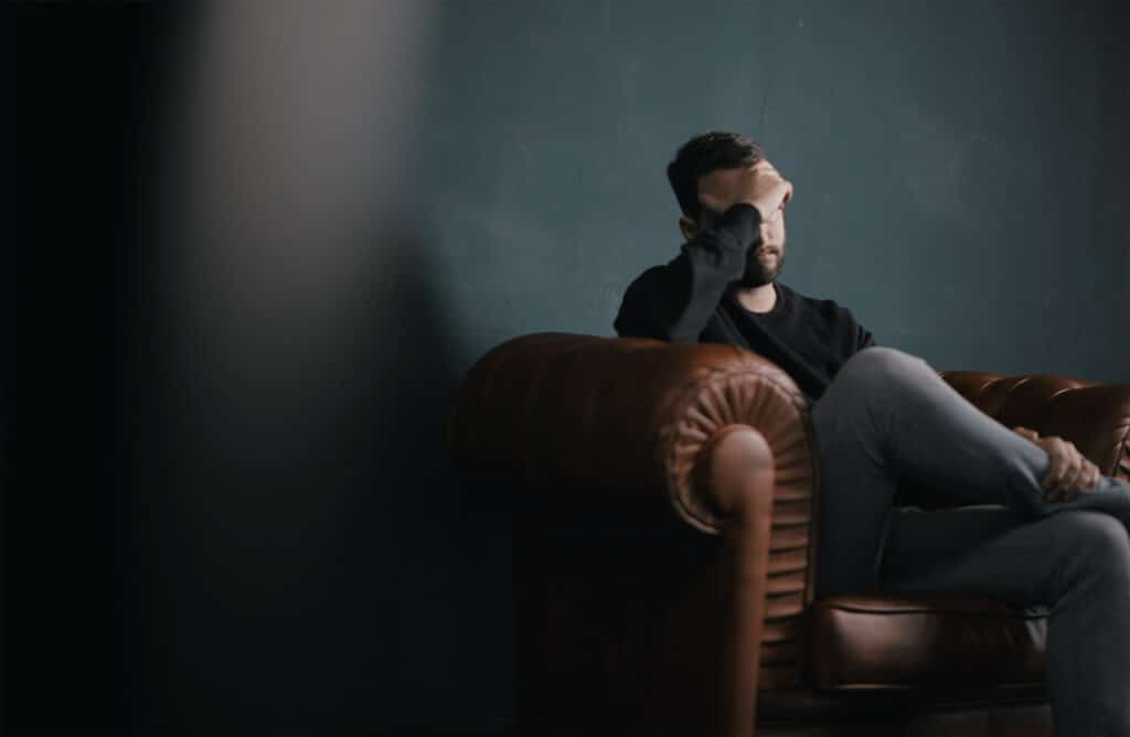 man sitting on a couch with his hand touching his forehead and looking problematic